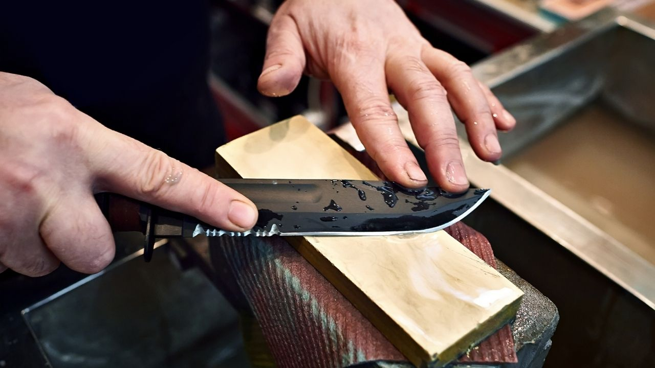 photo of a person sharpening a fixed blade knife