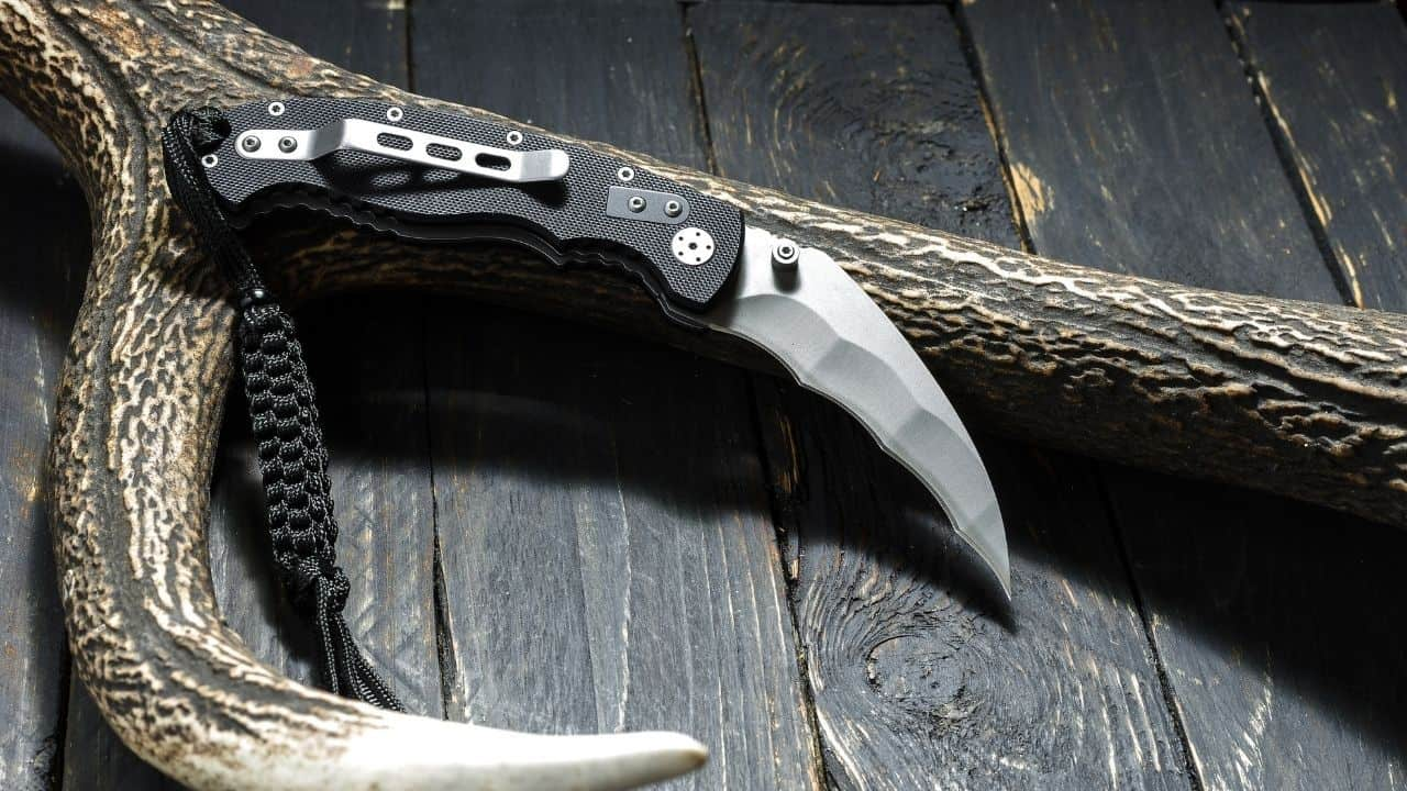 photo of a folding karambit knife leaning up against an antler