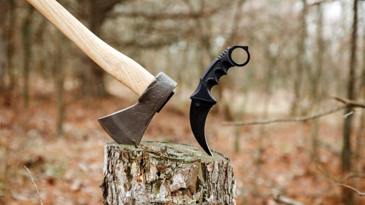 photo of a karambit knife and a hatchet stuck into a stump in the woods