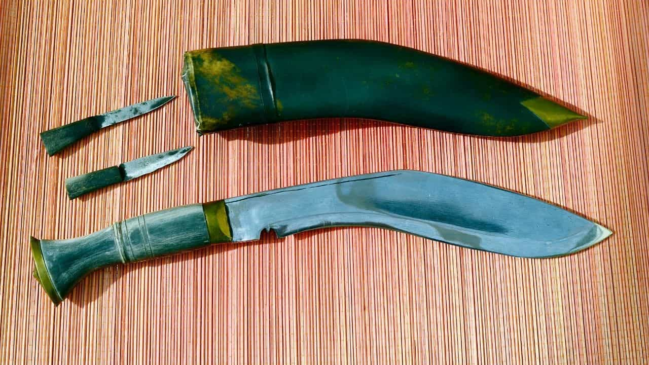 photo of a kukri knife and sheath laying on a striped surface with two smaller blades