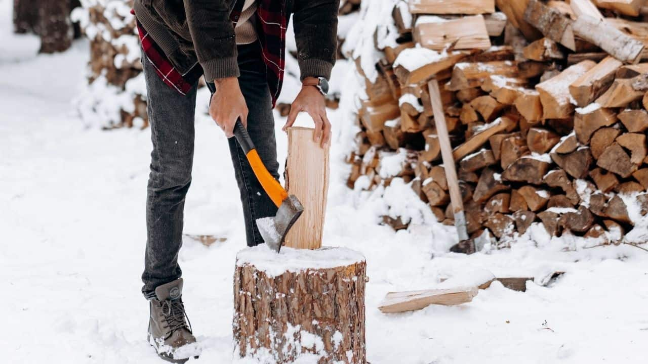photo of a man getting ready to chop a log with an orange hatchet