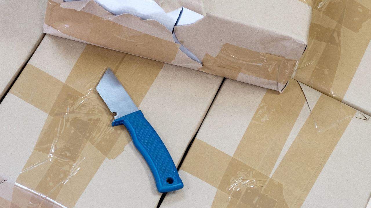 photo of cardboard boxes with lots of tape and a knife