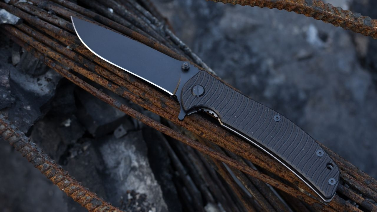 photo of a dark colored pocket knife on rusted metal