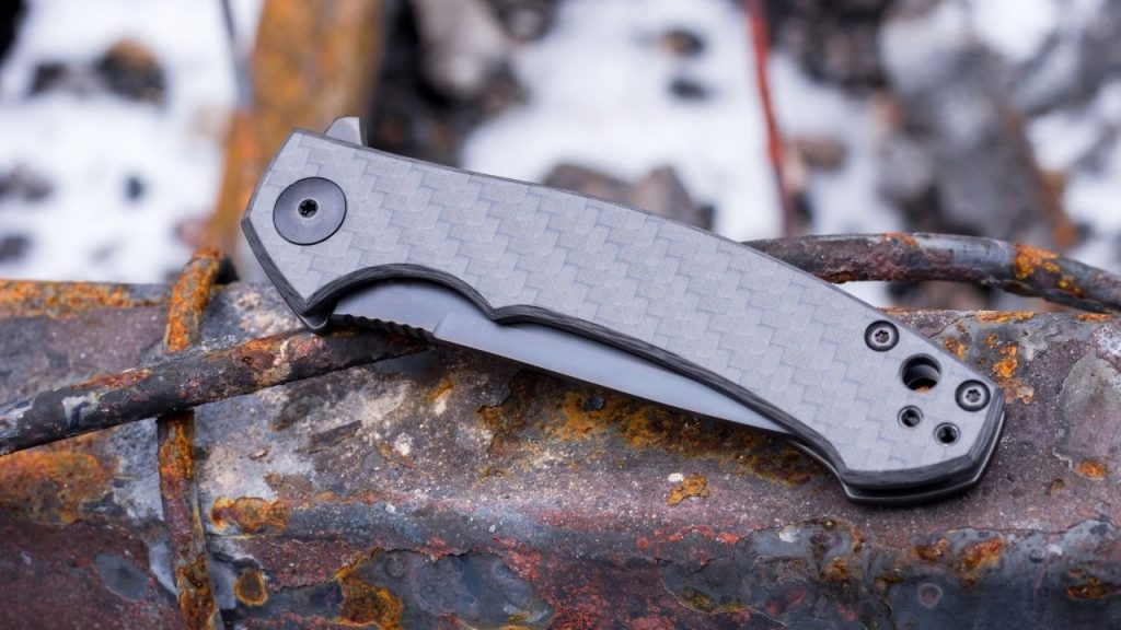 photo of a titanium folding knife closed on a rusty piece of metal