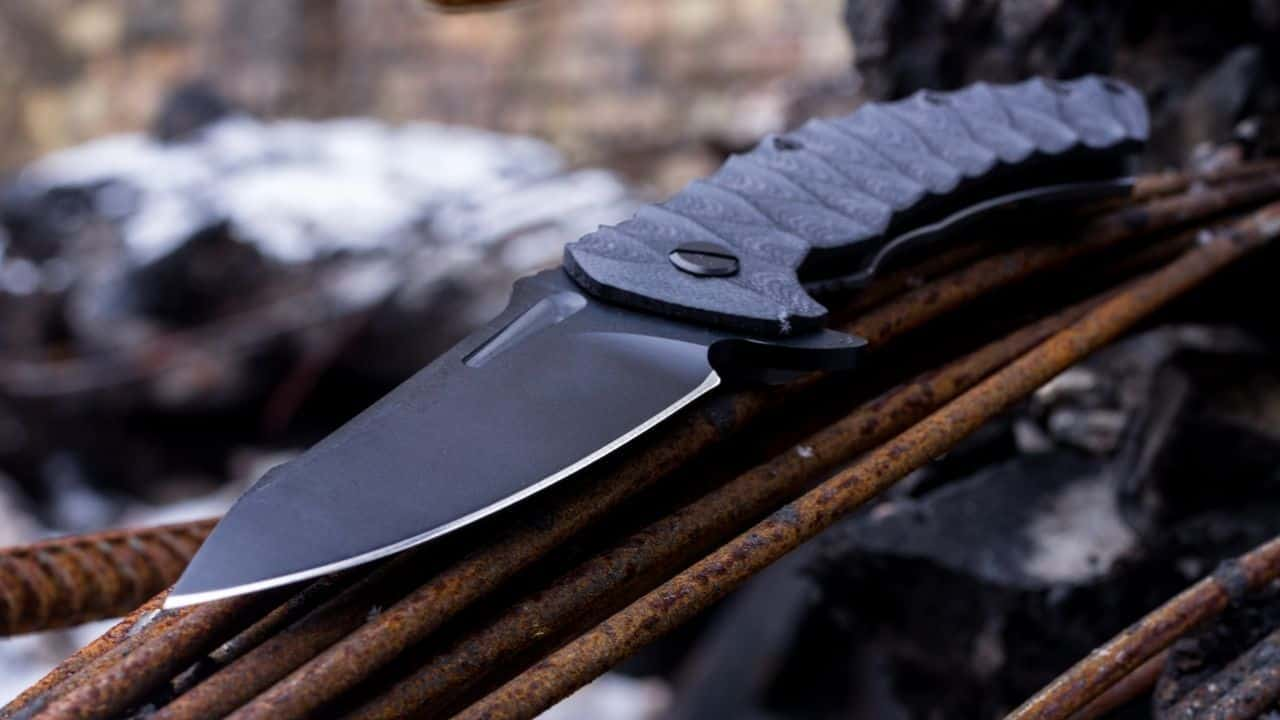photo of a titanium folding knife open while sitting on rusty metal rods