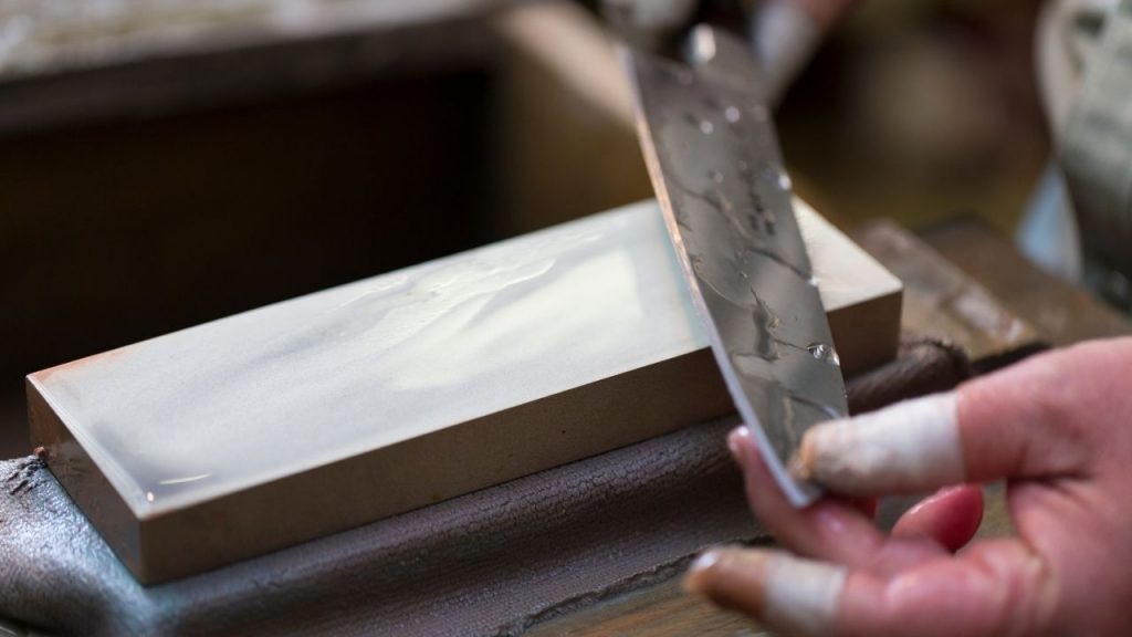 photo of a person sharpening a knife on a whetstone