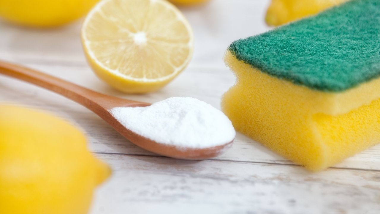 photo of a wooden spoon of baking soda next to a lemon and a sponge