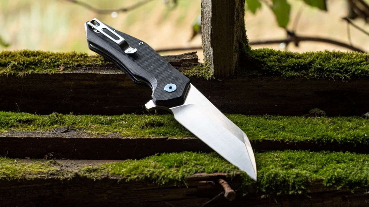 photo of a folding knife with wharncliffe style blade on mossy wood